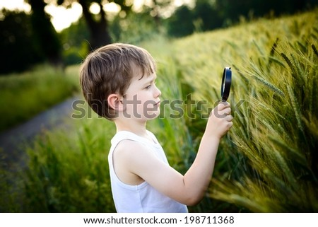 boy looks at the grain through a magnifying glass - stock photo