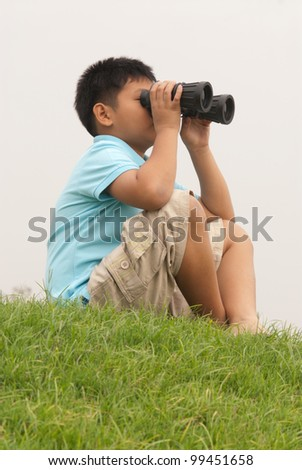 Boy looks into binoculars on top of hill . - stock photo