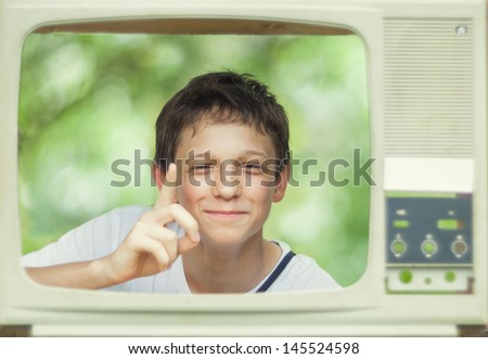 Boy looks out of the old TV - stock photo