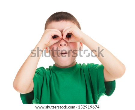 boy looks through his hands like binoculars - stock photo
