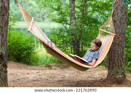 Boy lying in hammock reading a book outdoors