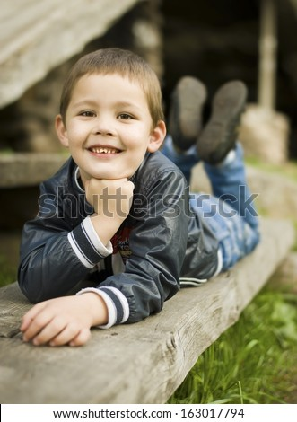 Boy lying on a bench in the park and trying to be a model on his father  - stock photo
