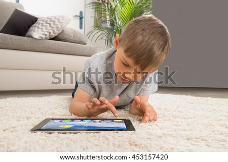Boy Lying On Carpet Using Digital Tablet With Multicolored Apps On It