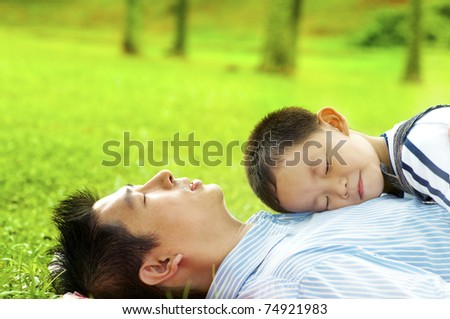 Boy lying on father. Father lying on green grass outside.