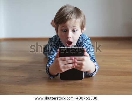Boy lying on the floor and reading electronic book - stock photo