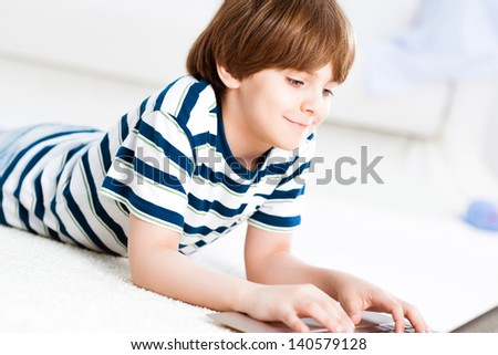 boy lying on the floor at home, working on a laptop - stock photo