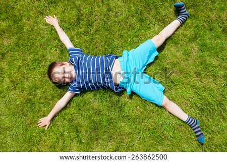 Boy lying on the grass - stock photo