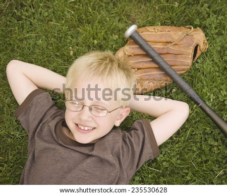 Boy Lying on the Ground with Baseball Glove and Bat - stock photo