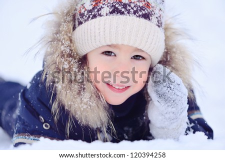 Boy lying on the snow. Portrait of a child. Winter and cold. Happy kid.