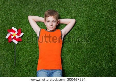 Boy lying with pinwheel  on green grass - stock photo