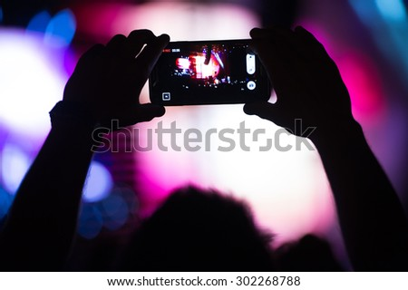 Boy makes photo with his smartphone to a concert to share the moment with friends on social networks, image with blurred and faded effect with grain - stock photo