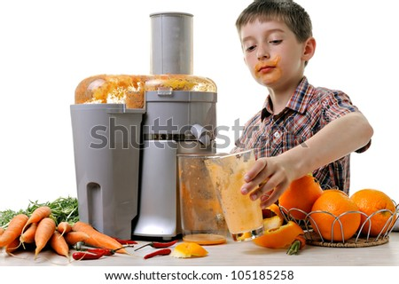 boy making fresh and healthy juice with a juice extractor - stock photo