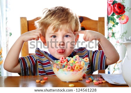 Boy misbehaving while eating breakfast cereal - stock photo
