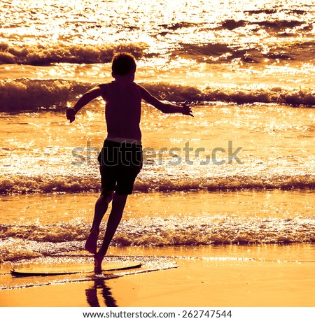 Boy moves on the surf board (alongside the sea shore) at sunset. Back view. (Brittany, France) Toned sunset photo. Freedom concept. - stock photo