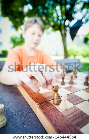 Boy moves piece in a chess game. Focus is on the hand - stock photo