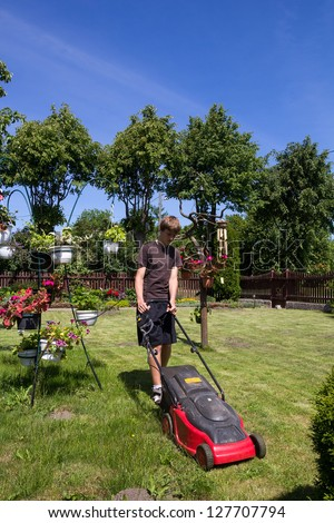 Boy mowing the garden with an electric lawn mower - stock photo
