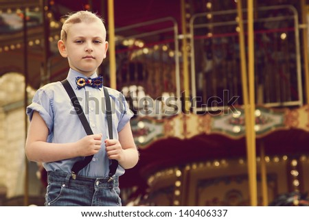 Boy near a game park attraction. A boy in a shirt with a stylish haircut and a butterfly. Boy waiting for a ticket to the roundabout. A boy wearing blue shirt and pants with suspenders.