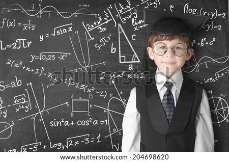 boy near blackboard with formulas - stock photo