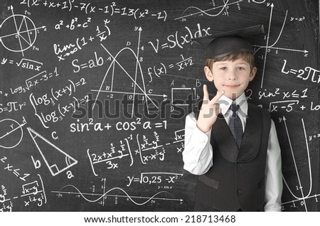 boy near blackboard with formulas - stock photo