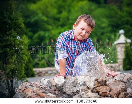 boy near the fountain in summer