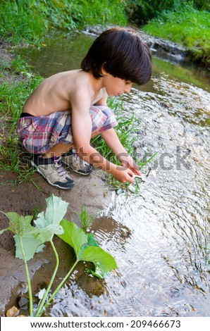 boy near the stream starts boat