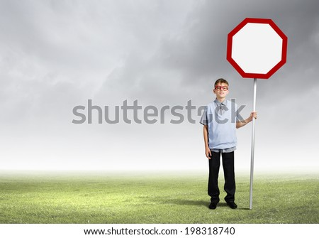 Boy of school age in glasses holding blank road sign - stock photo