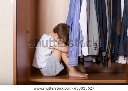 Boy of 6 years old sits in a cupboard with shirts and classical jackets of his father