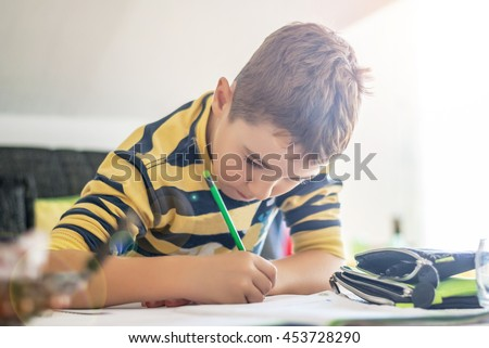 Boy of 8-9 years, writes homework at home after school