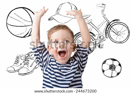 boy on a background of sports equipment. bicycle, ball, shoes, cap - stock photo