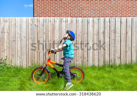 Boy on a bike in the garden - stock photo