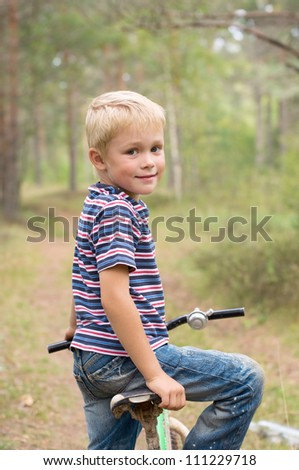 Boy on a bike is going to go on a forest path - stock photo