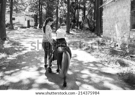 Boy on a horse on nature. Near the girl of his fears. They go down the path. Boy, horse, nature, path - The concept of active rest. Article about children's equestrian sport. - stock photo