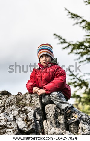 Boy on a peak looking curious outdoors
