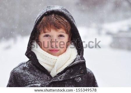 Boy on a snowy day in the park - stock photo