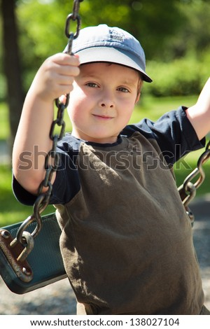 Boy on a swing in a playground
