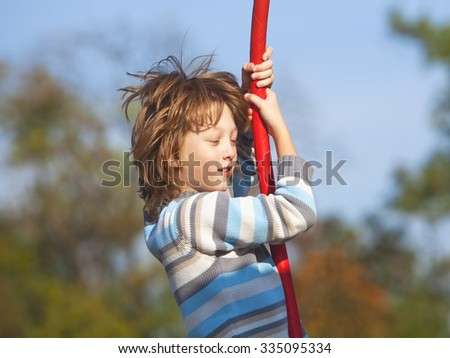 Boy on a Swing in the Playground - stock photo