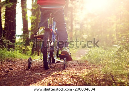 Boy on bike in the forest - stock photo