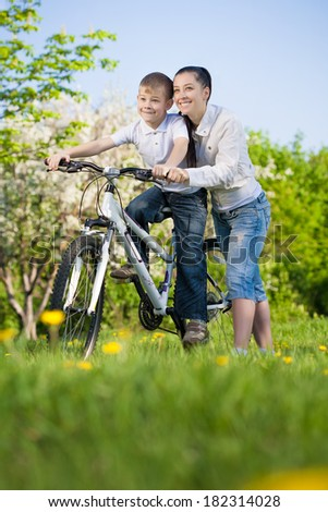 Boy on bike with mother - stock photo
