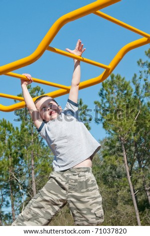 boy on monkey bars at park