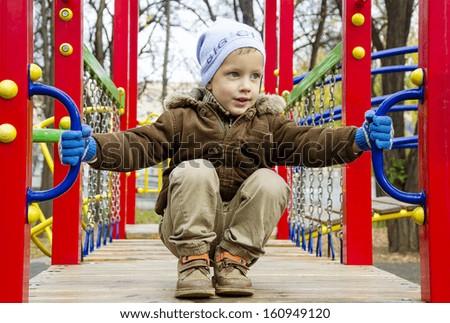 Boy on playground in cold autumn - stock photo