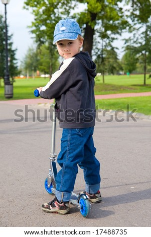 Boy on scooter in local park on a sunny afternoon - stock photo
