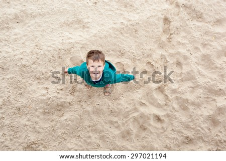 Boy on the beach looking up. Shoot from top  - stock photo