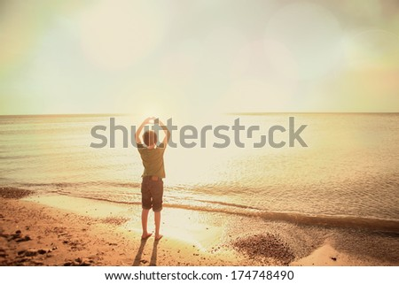 Boy on the beach making a heart shape with his hands - stock photo