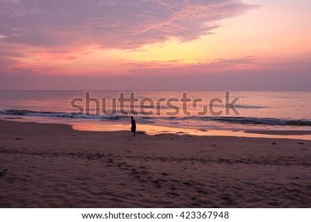 Boy on the beach with sunrise - stock photo