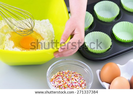 Boy or Girl Baking  cooking cakes just about to whisk the egg into the flour  - stock photo