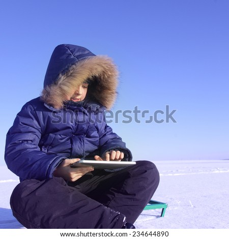 boy outdoors with tablet PC in winter snow time - stock photo