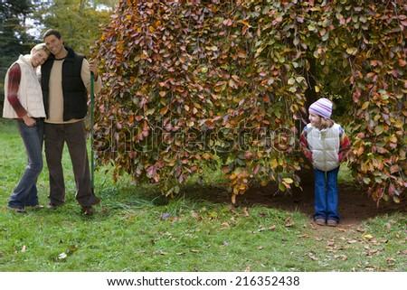 Boy peering at girl hiding in tree - stock photo