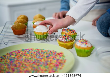 Boy placing cupcake on tray in the kitchen