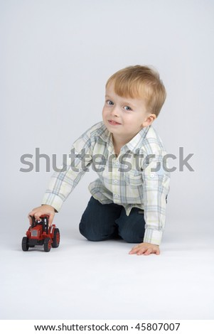 Boy plaies with toy - car,on egg white background.