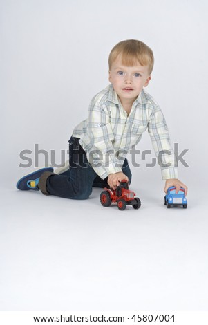 Boy plaies with toy - cars,on egg white background.